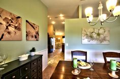 Green is the color of harmony, and the pale green walls pair harmoniously with the white beadboard, dark furniture and monochromatic photos in this not-to-formal dining room! Highland Homes' Remington IV model home in Ocala, Florida. #dreamhomes #decorating #decor #paint