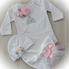 This precious white take me home gown and cap set is embellished with a sparkling rhinestone carriage fit for a princess. Topped off with beautiful chiffon and lace flowers and satin bows. The gown has fluffy chiffon tulle trim sewn around the elastic bottom. The matching cap completes the outfit, each of these stunning gowns is lovingly hand made for your special little girl. Made from Soft cotton/ spandex the gown and cap are so soft in addition to being beautiful. Perfect for that first…