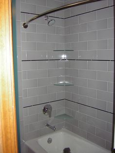 Hall bathroom / laundry room renovation.  Tub surround includes subway tile with custom rear corner design and front corner glass shelves.
