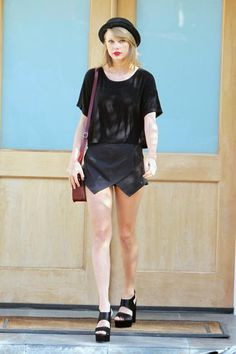 Taylor Swift stepped out in LA wearing a black origami-front Missguided skort that she styled with a loose black T-shirt, chunky Asos platform sandals, a Free People hat, and burgundy Cambridge Satchel bag.