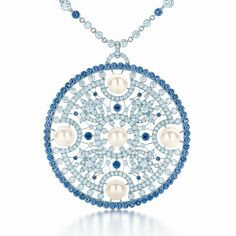 A medallion pendant of diamonds, Montana sapphires and cultured pearls, interlaced with platinum wire.