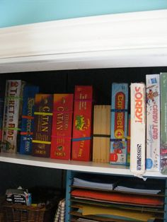 The Complete Guide to Imperfect Homemaking: A Simple Tip for Tidy Board Game Storage, inexpensive headbands wrapped around board game boxes, then stand the boxes up on your shelf