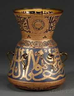 A gilt and enameled glass Mosque lamp, the slanting body and the trumpet-shaped neck decorated in blue and red enamels and gilt with calligraphy and floral scrolls, six lugs encircling the midsection. Egypt/Syria, circa 1801-1900