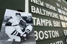 A photo of the late Boston Red Sox baseball player Johnny Pesky is displayed in front of the Green Monster left field wall and scoreboard, behind, at Fenway Park, in Boston, Sunday, Sept. 23, 2012. Ceremonies were held Sunday at the baseball park to honor the life of Pesky who was a player, manager, and coach for the team. Pesky died in August of 2012. (AP Photo/Steven Senne)