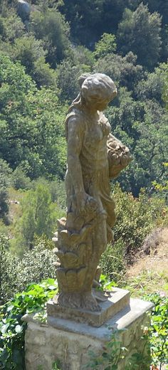 Eze Village, France - a statue resting on a cliff