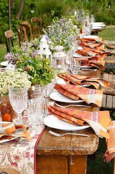 Wonderful PINK and ORANGE outdoor garden table setting! Love everything - the lines of plants and flowers on the table runner along the center of the table napkins are folded over the simple white plates!