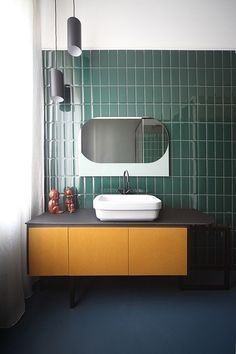 Green tiled bathroom with Shapes mirror