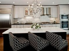 A true princess' kitchen! Stunning chandelier. Love the backsplash, centre island and those chairs!  #kitchen #chandelier #backsplash