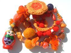 AprilO - Bunte Kette mit Matrioschka Die Kette mit Matrioschka besticht durch den Perlenmix in Orange. Filzkugeln, Häkelblume und die umhäkelte Pom