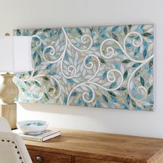 Tranquil tones and intriguing, reflective swirls give our wall panel a unique sense of serenity. Hand-carved, hand-painted and featuring glass mosaics, it can be hung vertically or horizontally, making it ideal for a wide range of spaces.