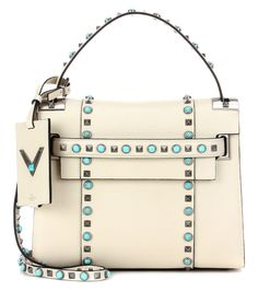 Valentino - My Rockstud Rolling Noir leather tote - Valentino's Rockstud Rolling Noir tote bag has been crafted in Italy from grainy ivory leather. Embellished with the label's iconic pyramid-shaped studs, this style also comes with shiny turquoise stones to further the luxe vibe. Tote your essentials in this roomy style by the top handle or switch to the shoulder strap to go hands-free. seen @ www.mytheresa.com