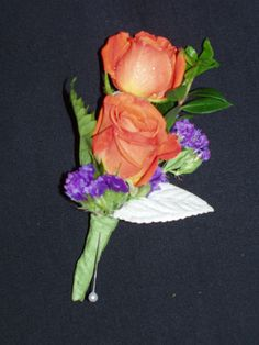 Orange spray roses with purple statice and leather leaf bout