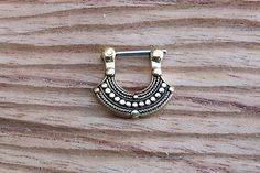 16g Septum Clicker by Flaming Bones    This piece has been cast out of yellow brass and has an F-138 implant grade steel pin which goes through the piercing.