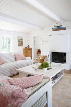 Takkatuli lämmittää isommassa mökissä viileinä iltoina. Kalusteita Nina on ostellut antiikkiliikkeistä vuosien varrella, joitakin on teetetty tänne. Vanhat kalusteet saivat vaalean maalipinnan samalla kerralla seinien ja kattojen kanssa.