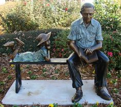 Quality time  --  Inter-generational sculpture of an older man reading a book as a young girl gazes at him.  by Randolph Rose