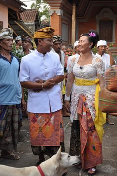 A Balinese Wedding: here is the bride and groom in traditional Balinese dress. The man wears a gelong and a sarong. The woman wears a kebaya,sash and sarong.