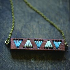 """Trunbull Necklace. Inspired by the sunrise; a time for new beginnings. This necklace is composed of laser cut wood that has been sanded, stained, and sealed for longevity. The 18"""" antique bronze chain is hypoallergenic. This makes for a great, colorful accessory that doesn't overpower your outfit. Colors: Blue, White & Blue. Yarn & string jewelry"""