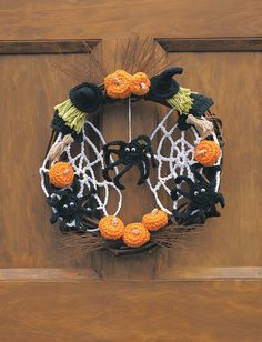 Trick or Treat | Spooky Halloween wreath with witches, spiders and pumpkins. Shown in Lily Sugar 'n Cream. Size 4mm (U.S. G or 6) crochet hook. Yarnspirations
