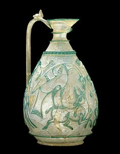 Corning Ewer, ca. 1000 Western Asia or Egypt Glass, cut and engraved; H. at rim 6 1/4 in. max. Diam. 3 5/8 in. The masterpiece of Islamic art and of colored glass production worldwide. The shape and quality of the decoration have parallels in rock-crystal ewers made for the Fatimid caliphs of Egypt in the late 10-11th C. Relief-cut glass of such quality, however, is usually attributed to the Iran, where both the Corning and the Buckley Ewers reportedly were found.