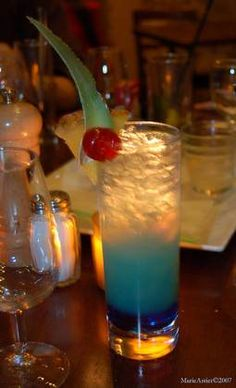 BLUE LAGOON - Ice cubes,  2 oz vodka,  2 oz blue curacao liqueur,  lemonade,  Maraschino cherries for garnish.    Pour the vodka and curacao over ice in a highball glass. Top up with lemonade and garnish with cherries.