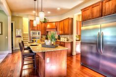 The Alki floorplan has a beautiful large open island kitchen with slab granite countertops, pro grade stainless steel appliances, and beautiful Cabinetry.