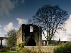 Whalley Abbey Gatehouse, England.   The two-storey gatehouse is all that remains of 13th century Whalley Abbey. The abbey was founded by the Cistercian order in 1296, and grew to become the second most powerful abbey in Lancashire. The north west gateway and associated walls still stand in a lovely setting beside the River Calder.