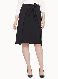 Exclusivité Contemporaine     L'esprit classique d'une jupe noire élégante dans une version deux niveaux à nouer à la taille   Coupe droite aux genoux   Fermoir zip invisible sur le côté   Crêpe fluide extensible    Le mannequin porte la taille 4