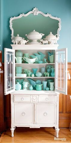 Collection of aqua pottery in a white cabinet.