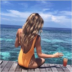 Bright pastel orange one piece with beautiful blue ocean water. Take me here!