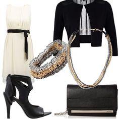 Il nero e il bianco sono da sempre i colori dell'eleganza e raffinatezza. Il vestito leggero, nella sua trasparenza, viene messo in risalto dal colore nero della giacca, della borsa e delle scarpe e impreziosito dagli accessori dai colori brillanti e preziosi.
