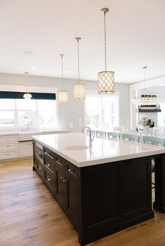 Small Regina Andrew Metal Patterned Pendant Fixture over Kitchen Island topped with white quartz countetop.. Millhaven Homes.