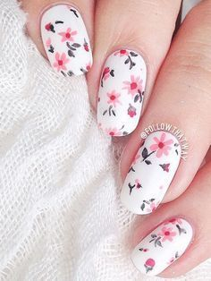 Give your nails a bright spring feel with this flower inspired nail art design. The falling pink flowers look perfect against the white base color of the nails. #nailart #springnailart