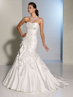 AA064 swirling bustles that frame a modified mermaid skirt flaring from a dropped waist. Lace appliqués with hand-beading accentuate the fitted bodice which is topped by an asymmetrically tailored bust with softly curved strapless neckline. A chapel length train, sexy corset back and removable straps complete with glamour this gown