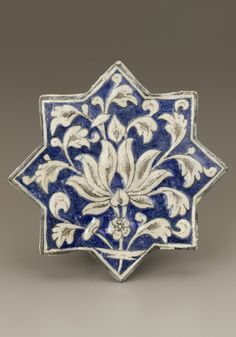 Star-shape tile  early 14th century    Il-Khanid period     Stoneware, composite body painted under clear glaze.  H: 19.7 W: 19.7 D: 1.9 cm   Iran