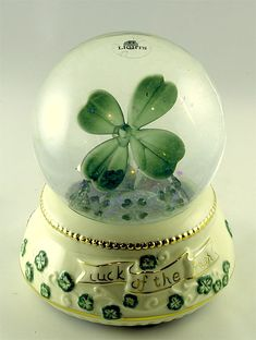 Luck of the Irish LIGHTED glittery water globe. Plays 'When Irish Eyes are Smiling'. Porcelain gilt trimmed base with green shamrocks and a big one inside.
