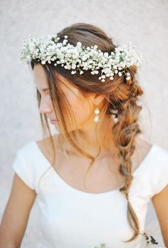 Brides.com: . This bride achieves boho perfection with a gorgeous wreath of baby's breath adorning her loose sideswept braid paired with a simple scoop neck dress.