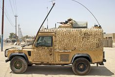 """Deployed as part of a security detail, the top cover sentry of a British Army """"Snatch"""" armoured Landrover patrol vehicle uses his SUSAT sight to scan for signs of trouble. Basrah 2005."""