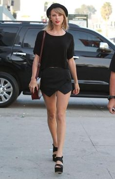 Taylor Swift in a black origami skort and bowler hat.