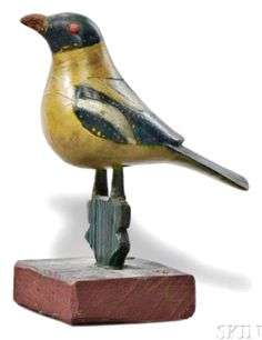 Realized: $20,910. Description: Carved Songbird Figure, by the Virginville Carver, America, c. 1875-1925, red eyes, yellow body, wings in blue-black, cream, and yellow, tail with gold bead accents, (minor wear), ht. 7, lg. 7 in. Minor paint loss to the top of the head, back and tail feathers.