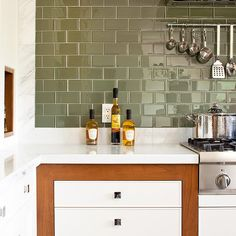 green tile is limited to one wall of the kitchen; a low marble backsplash accents the adjacent sink wall, continuing the veining pattern of the kitchen's marble countertops.