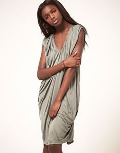Chalayan Grey Line Dress With All Over Pleat & Drape Detail    Draped dress from Chalayan Grey Line. Crafted in a soft-handle fluid jersey with a shine finish. Featuring a deep v-neckline, sleeveless styling with softly gathered shoulders, a signature draped design with a centre seam detail to the front, a cocoon shape and an exaggerated draped overlay to the reverse.