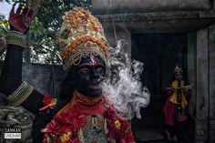 Fuming goddess - The bahurupi, roughly translating to 'many forms or faces' are a community that dress up like Hindu gods to collect alms. As faith recedes, this community has become an unseen casualty. Here, dressed up like the goddess Kali, a bahurupi takes puffs from his bidi before setting off to work. IN the background is his daughter, dressed up as Krishna.