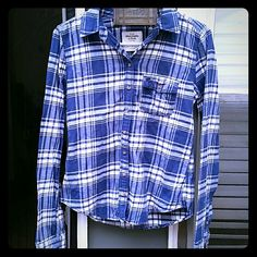 Campfire Flannel Shirt Very cozy, classic blue and white plaid. Brown buttons on torso, sleeves also have buttons to roll-up if desired. Slightly longer in back, sits at hips. 100% cotton Abercrombie & Fitch Tops Tees - Long Sleeve