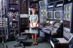 U.S. Army audiovisual technician stands at her videotape editing station, 1973.