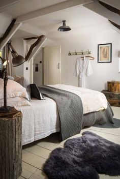 The Fable, luxury self-catering thatched cottage near St Agnes and Truro in Cornwall, with pale wooden floors, sheepskin rugs and rustic wooden bedside tables making this a cosy modern rustic bedroom