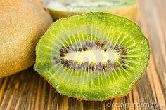 Photo about Two Kiwi Fruits sit on the cutting board on cut in half. Image of halves, organic, half - 94989979 Video Footage, Kiwi, Whole Food Recipes, Cutting Board, Perspective, Seeds, Organic, Fruit, Green