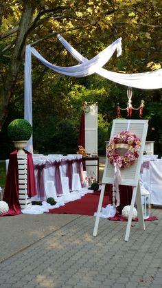 A zöld -  bordó - fehér hármasa garancia a szabadtéri esküvő eleganciájára. A bevonuló szőnyeg optikailag felerősíti a fehér székszoknyákat. Helyszín: Derekegyházi Vadászház