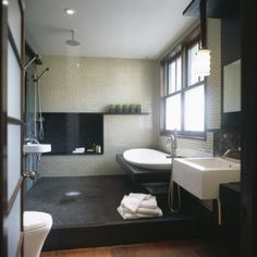I really like this shower/bath combo.  I also love the tiles with the dark wood, and the shelf on the far wall.  The sink in the shower is to facilitate shaving while in the shower :)