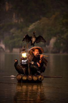 Cormorant fisherman taking a vape - Xingping, China