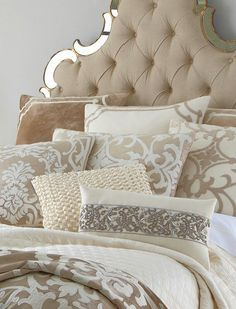 Tufted headboard and lots of pillows in different shapes, sizes and patterns. Custom bedspread too.